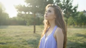 Portret van vrij jonge vrouw in het toevallige stellen in platteland en het bekijken camera in zonlicht stock footage