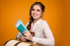 Portret van vrij jonge vrouw met haar paspoort en kaartjes in haar die hand over de gele achtergrond, het glimlachen wordt geïsol stock afbeelding