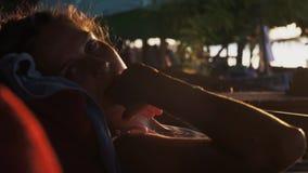 Portret van vrij jonge vrouwenzitting op chaise-longue buiten bij zonsondergang stock video