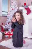 Portret van vrij zoet meisje dichtbij een open haard in Kerstmis stock foto's