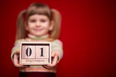 Portret van vrolijk die meisje op rode greep houten die kalender wordt geïsoleerd op fir september, nadruk op kalender wordt gepl Royalty-vrije Stock Foto's