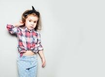 Portret van vrolijk meisje in plaidoverhemd en jeans die zich tegen grijze achtergrond bevinden royalty-vrije stock afbeelding