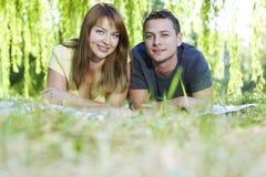 Portret van vrolijk paar dat op het gras legt stock foto