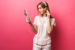 Portret van vrolijke gelukkige meisje het luisteren muziek in oortelefoons die het lege scherm van mobiele telefoon op roze achte stock fotografie