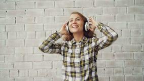 Portret van vrolijke jonge dame die en het zingen aan radio in draadloze hoofdtelefoons dansen luisteren die in wijfje dragen stock video