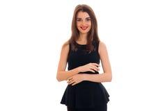 Portret van vrolijke jonge donkerbruine vrouw in modieuze zwarte kleding die die en de camera stellen bekijken op wit wordt geïso Royalty-vrije Stock Foto's