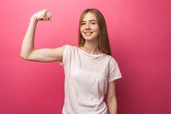 Portret van vrolijke jonge meisjes buigende bicepsen op roze achtergrond, leuk en aantrekkelijk, stock afbeelding