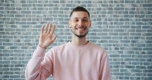 Portret van vrolijke jonge mens golvende hand en het bekijken camera met gelukkig gezicht stock video