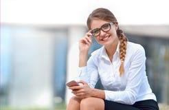 Portret van vrolijke jonge vrouw die smartphone in openlucht gebruiken Royalty-vrije Stock Foto