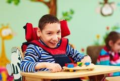 Portret van vrolijke jongen met handicap op revalidatiecentrum voor jonge geitjes met speciale behoeften royalty-vrije stock foto's