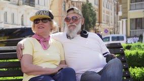 Portret van vrolijke modieuze oude mensen die op de bank in de stad ontspannen stock footage