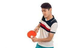 Portret van vrolijke sportman die een pingpong uitoefenen die en op een geïsoleerd spel op witte achtergrond concentreert zich Royalty-vrije Stock Foto's