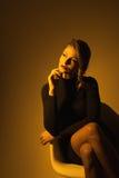 Portret van vrouw als voorzitter op donkere gele achtergrond Royalty-vrije Stock Afbeelding