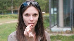 Portret van vrouw die een stuk van worst in het Park eten stock videobeelden