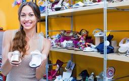 Portret van vrouw die voor paar schoenen voor jong geitje zorgen Stock Foto's