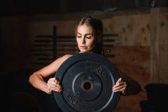 Portret van vrouw in gymnastiek met plaat 5 kg stock fotografie