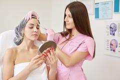 Portret van vrouw het bekijken in spiegel cosmetologistkabinet en het krijgen van anti het verouderen injectie voor haar voorhoof stock foto's
