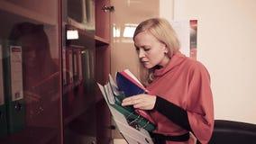 Portret van vrouw in het bureau die noodzakelijke documenten zoeken stock footage