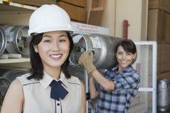 Portret van vrouw het glimlachen met de vrouwelijke cilinder van het fabrieksarbeider dragende propaan op achtergrond Stock Foto