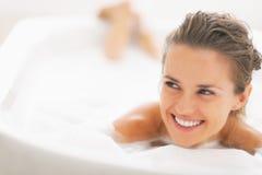Portret van vrouw het leggen in badkuip en het kijken op exemplaarruimte royalty-vrije stock afbeeldingen