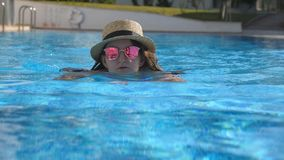 Portret van vrouw het zwemmen in pool in zonnebril en hoed tijdens de zomervakantie Het jonge mooie meisje ontspannen in bassin stock videobeelden