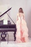 Portret van vrouw met grote piano Stock Foto