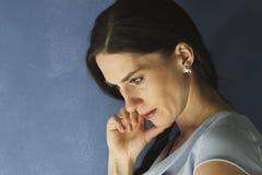 Portret van vrouw met hand op haar gezicht die neer eruit zien royalty-vrije stock afbeelding