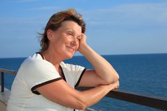 Portret van vrouw op middelbare leeftijd op balkon over overzees stock afbeeldingen