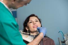 Portret van vrouw in tandkliniekbureau Tandarts die en kleur van de tanden controleren selecteren tandheelkunde stock foto