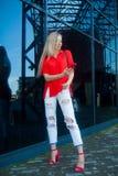Portret van vrouw van het schoonheids de glimlachende blonde in rood overhemd met smartphone dichtbij het bureau Exemplaar-ruimte Royalty-vrije Stock Foto