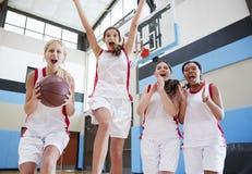 Portret van Vrouwelijk Middelbare schoolbasketbal Team Celebrating On Court stock foto's