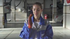 Portret van vrouwelijk specialisten verpletterend stof en vuil van handschoenen na het harde werk met de machine in de autodienst stock videobeelden