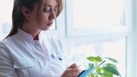 Portret van vrouwelijke arts met tabletcomputer in haar bureau stock video