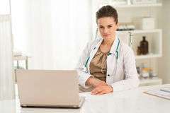 Portret van vrouwelijke artsenzitting bij een bureau in het bureau Stock Foto's