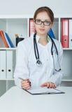 Portret van vrouwelijke geneeskunde arts die zilveren pen houden die iets op klembordclose-up schrijven Stock Foto