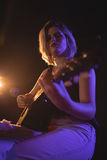 Portret van vrouwelijke gitarist die in muziekoverleg presteren royalty-vrije stock afbeelding