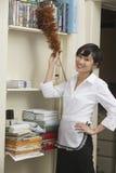 Portret van vrouwelijke huishoudster die plank bestrooien royalty-vrije stock foto's