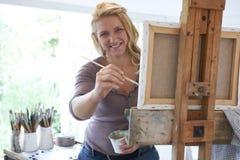 Portret van Vrouwelijke Kunstenaar Painting In Studio stock foto's