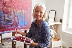 Portret van Vrouwelijke Kunstenaar Working On Painting in Studio royalty-vrije stock foto's