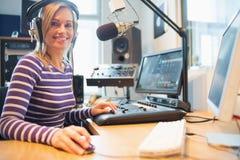 Portret van vrouwelijke radiogastheer die computer in studio met behulp van stock afbeelding