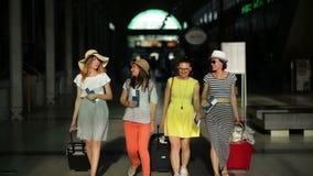 Portret van vrouwelijke toeristen met documenten, kaartjes, en grote koffers in handen bij de luchthaven Vier vrienden gaan stock videobeelden
