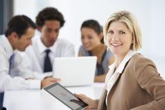 Portret van Vrouwelijke Uitvoerende Gebruikende Tabletcomputer met Bureauvergadering op Achtergrond Stock Afbeelding