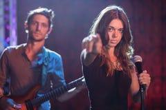 Portret van vrouwelijke zanger met mannelijke gitarist die bij nachtclub presteren stock afbeeldingen