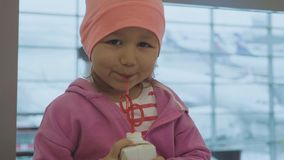 Portret van wat kind het drinken sap en het onderzoeken van de camera bij luchthaven stock video