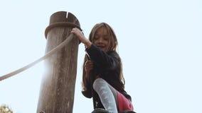 Portret van weinig aanbiddelijk meisje op speelplaats Het leuke glimlachende 6 éénjarigenmeisje gaat over hindernissen op vrolijk stock videobeelden