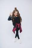 Portret van weinig hipstermeisje in bommenwerpersjasje posing Krullend modern kapsel Het tonen van vrede door vingers Het glimlac Royalty-vrije Stock Foto's