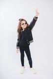 Portret van weinig hipstermeisje in zonnebril posing Krullend modern kapsel Het tonen van vrede door vingers Het glimlachen Stock Foto's