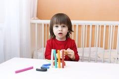 Portret van weinig jongen in rood overhemd met playdough Royalty-vrije Stock Foto