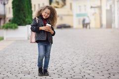 Portret van weinig krullend hipstermeisje in glazen met koffie Stedelijke stijl De herfst Royalty-vrije Stock Foto's