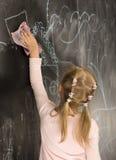 Portret van weinig leuk meisje die op het bord schrijven Stock Foto's